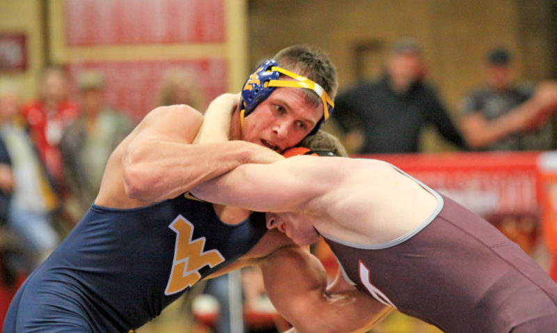 West Virginia's Jacob A. Smith grapples with Virginia Tech's Jared Haught during a college wrestling match Sunday at the PHS Field House. Photo by Michael Uhl.