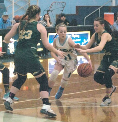 By Joe Albright Parkersburg Catholic's Madeline Huffman (31) splits Notre Dame's Taylor Martino (23) and Clare Cistaro (1) on her way to the basket during the Crusaderettes' 64-55 win over the Fighting Irish Monday.