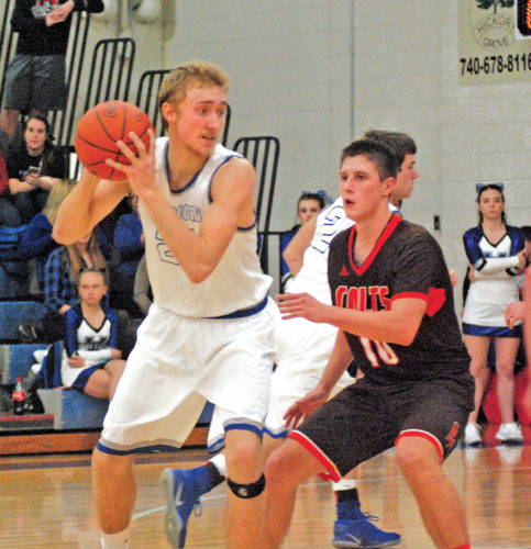 Warren's Chase Weihl, left, spots up with the ball as Meadowbrook's Justin Cork defends during a high school basketball game Tuesday in Vincent. Meadowbrook won, 50-49. Photo by Jordan Holland.