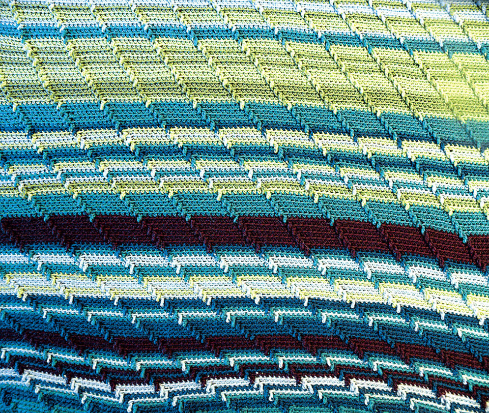 """Photo by Jeff Baughan The pattern of  the temperature blanket is called """"Apache Tears"""" on Pinterest.  The blanket measures 60 inches wide by 100 inches long."""