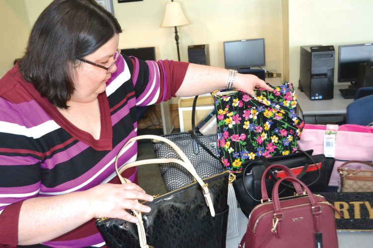 Photo by Peyton Neely Amanda Haney-Cech, auction coordinator, organizes the purses that will be sold at the purse auction scheduled Thursday by United Way of Washington County.