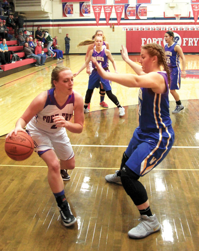 Photo by Tom Perry Fort Frye's Tanner Booth, left, makes a move with the ball against Warren defender Emily Jackson Monday night during the Cadets' 51-39 upset victory over the Warriors.