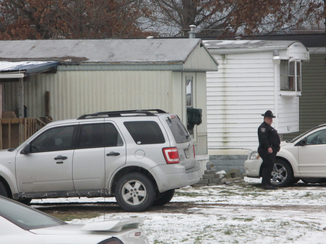 A deputy stands outside a mobile home on Nova Road in Mineral Wells where two people were shot this morning. A suspect remains at large, Sheriff Steve Stephens said.