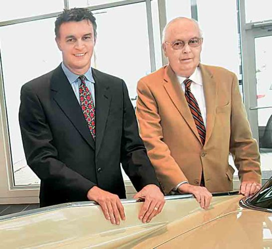 File Photo Dan Wharton Jr., left, and Dan Wharton Sr. stand behind the tailfin of a Cadillac in the Wharton Auto Group Cadillac showroom on Seventh Street in Parkersburg. The business marked its 70th anniversary in October.