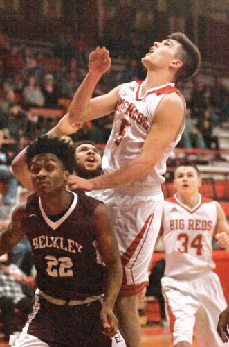 Parkersburg High's Parker Miller (5) looks to grab a rebound off a missed shot while Woodrow Wilson's Isaiah Francis (22) tries to figure out what is going on during the Big Reds' 85-71 win over the Class AAA, No. 5 Flying Eagles Friday night at PHS Memorial Fieldhouse.  Photo by Joe Albright.