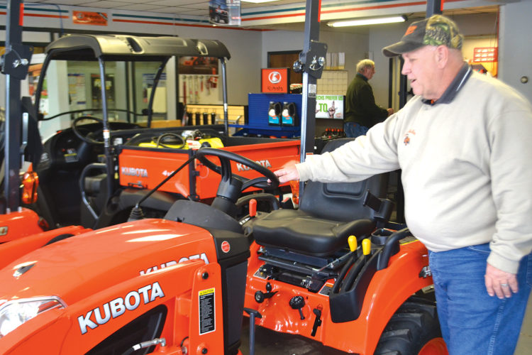 Photo by Peyton Neely Roger Moorison, store manager for Lashley Tractor Sales, inspects one of the lawn mowers at the Marietta store.