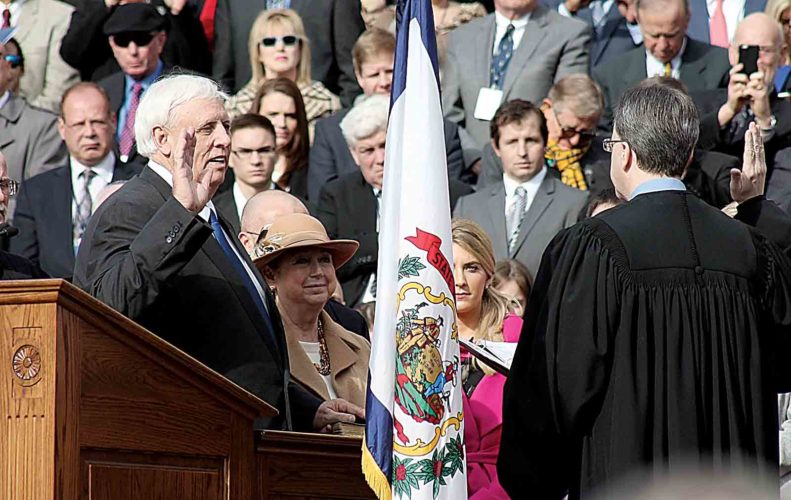 As he becomes West Virginia's 36th governor, Jim Justice takes the oath of office from Chief Justice Allen H. Loughry II on Monday during the inaugural ceremony at the state Capitol in Charleston. Justice's wife, Cathy, holds the Bible as Justice takes the oath. (Photo by The West Virginia Press Association)