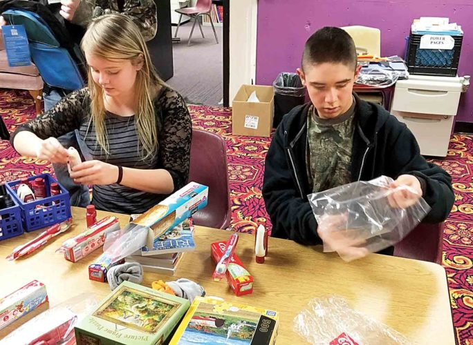 Fourteen-year-olds Katerina Floyd, left, and Joseph Whipkey, right, gather hygiene items to go in backpacks for homeless teens, part of a public service project members of the Parkersburg Boys and Girls Club performed Monday in honor of Martin Luther King Jr. Day. (Photo by Michael Erb)
