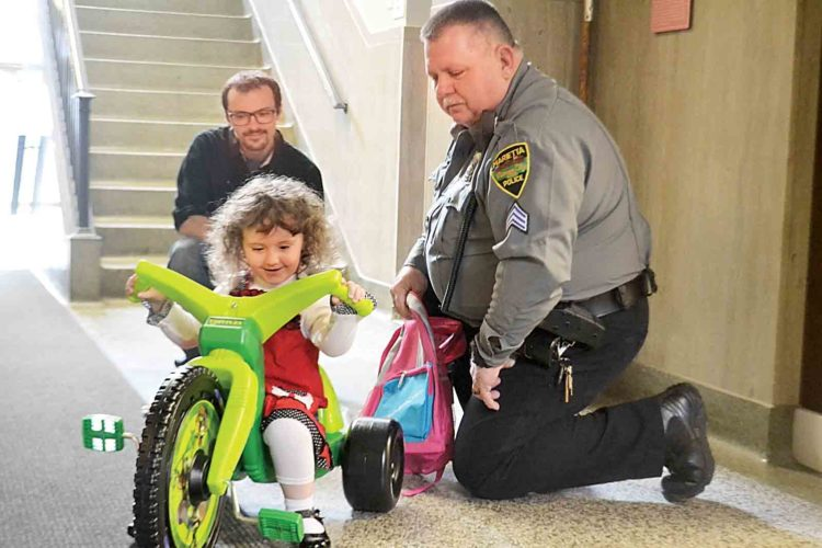 Bailey Clipner, 3, of Marietta rides her Teenage Mutant Ninja Turtle big wheel tricycle given to her by Sgt. Len Ritchie at the Marietta Police Department on Monday afternoon. (Photo by Peyton Neely)