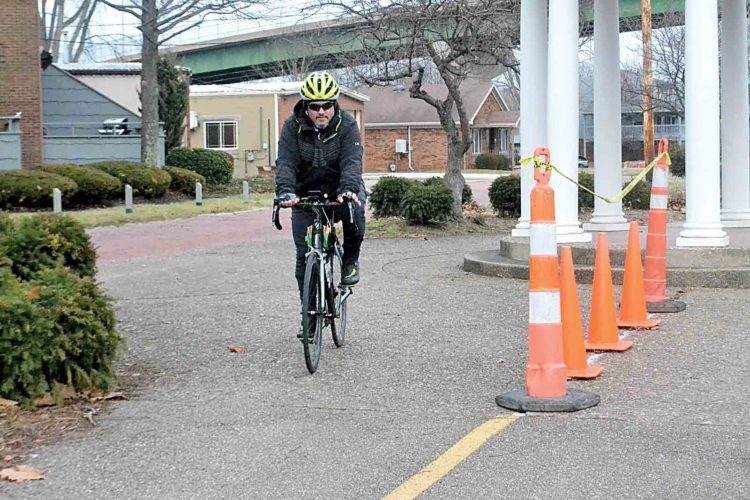Michael Uhl, 50, of Williamstown passes by cones marking a crack in the Marietta River Trail along the Ohio River during a bike ride. (Photo by Peyton Neely)