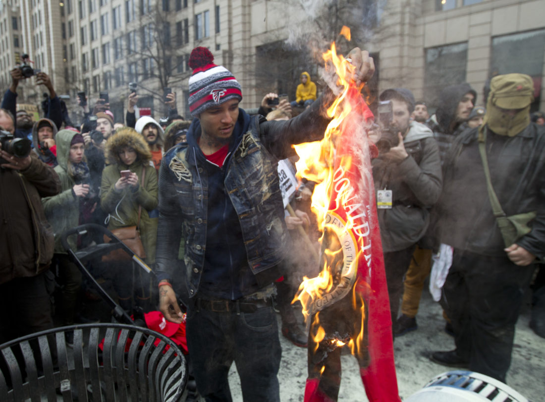 AP Photo A protester burns a Donald Trump shirt during a demonstration downtown Washington Friday.