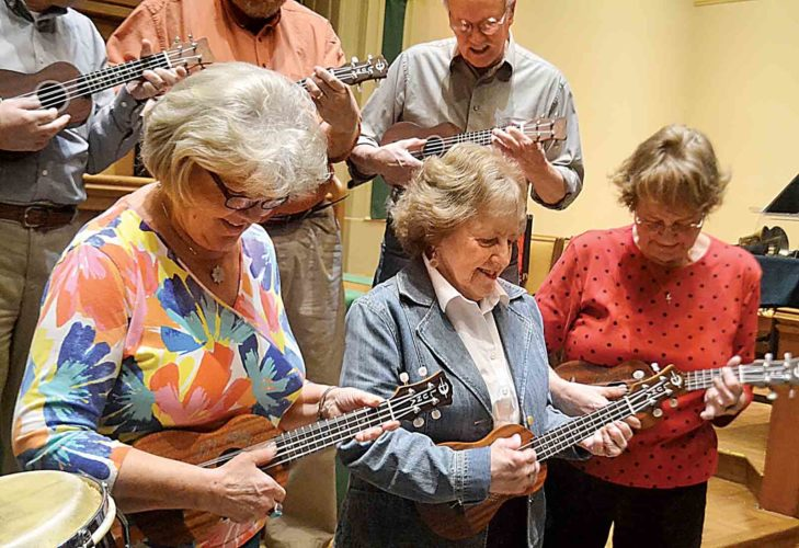 Photo by Peyton Neely Members of the new ukulele choir at Christ United Methodist Church in Marietta practice strumming on their instruments Wednesday evening at the church.