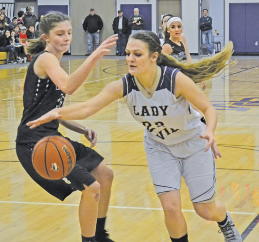 St. Marys' Amanda Cox, right, tries to get around Ritchie County's Andrea Kirk during a high school girls basketball game Friday. Photo by Ron Johnston.