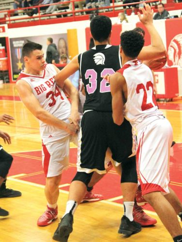 Photo by Tom Perry Parkersburg's Tyler Lawrentz (34) and Kionte Peacock (22) defend Riverside's TJ Wood during a high school boys basketball game Monday night at Memorial Fieldhouse.