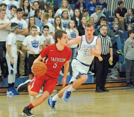 Jackson's Carson Spohn (5) handles the ball as Warren's Kyler Dennis defends during a high school boys basketball game Friday night in Vincent. Photo by Jordan Holland.