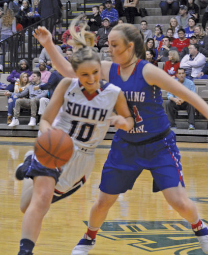 Parkersburg South's Jordan Johnson, left, tries to dribble past Wheeling Park's Josie Daugherty during Ohio Valley Athletic Conference 5A championship basketball action Saturday in St. Clairsville, Ohio. Photo by Josh Strope.