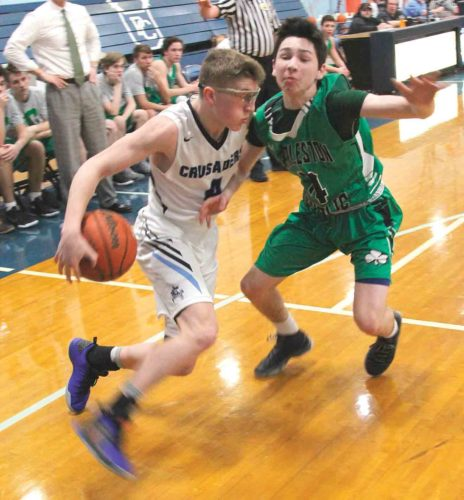Photo by Tom Perry Parkersburg Catholic's Cade Ullman, left, dribbles behind the back as Charleston Catholic's Robbie Williams defends during a high school boys basketball game Monday.