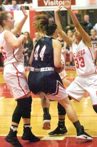 Parkersburg's Madi Mace (35) and Bre Wilson (33) defend Parkersburg South's Allie Taylor (44) on her way to the bucket Monday night during the Big Reds' 66-63 victory over the Patriots. Mace and Wilson combined for 40 points for PHS.  Photo by  Joe Albright