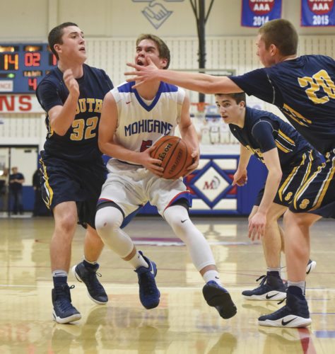 Morgantown's Torin Hanson makes contact with Parkersburg South's Bobby Foggin's hand as Cole Plants (right) and Brayden Mooney (32) apply additional pressure during a high school basketball game in Morgantown.