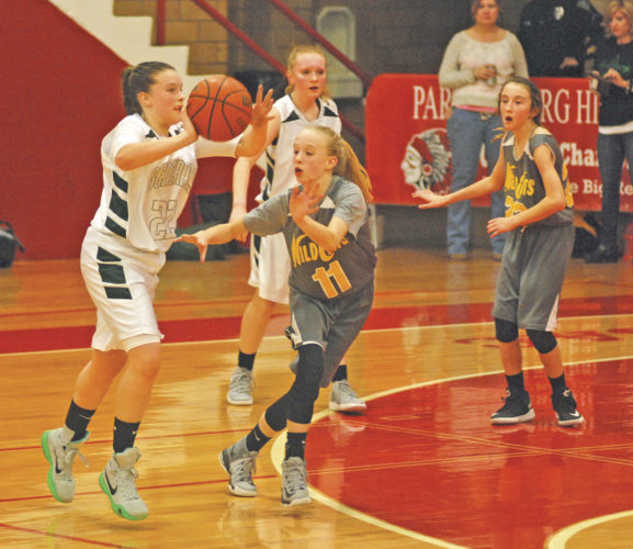 Jackson's Brilynn Florence passes to a teammate while Hamilton's Taneekah Longwell defends during the Wood County Middle School 6th grade championship game Thursday inside Memorial Fieldhouse. The Generals outlasted the Wildcats, 37-28. Photo by Jay W. Bennett.