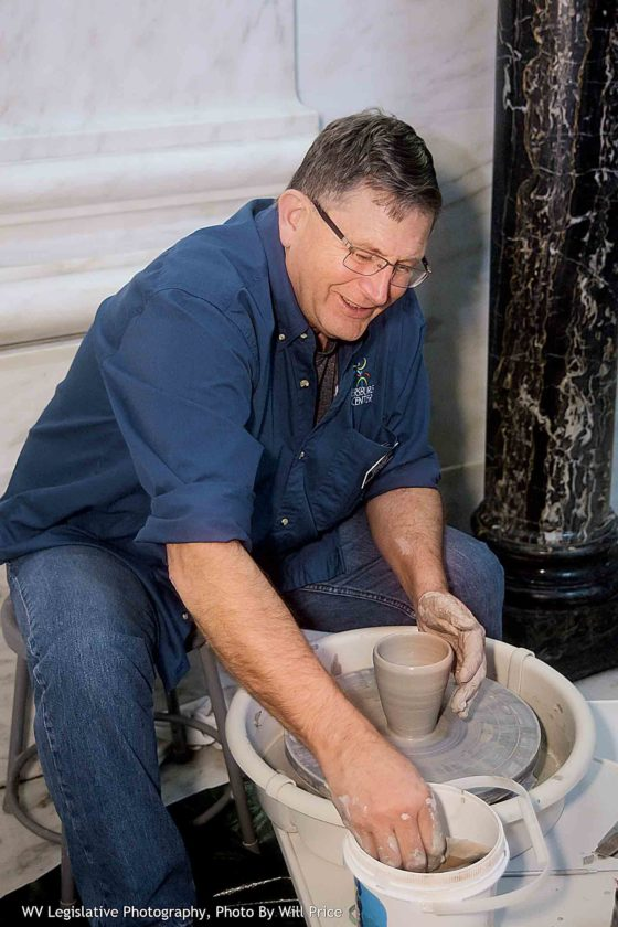 Photo by Will Price, West Virginia Legislative Photography Vance Hewitt, a potter and board member of the Parkersburg Art Center, on Wednesday demonstrates how pottery is turned on a potter's wheel at Arts Day at the West Virginia Legislature.