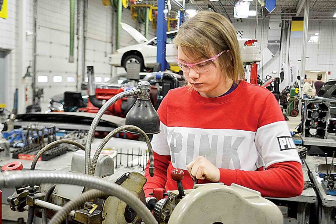 Photo by Peyton Neely Brittany Reed, 20, of Williamstown, grinds valves for a truck during her diesel mechanics class.