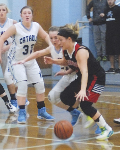 Ravenswood's Claudia Cubides drives past Parkersburg Catholic's Madeline Huffman during a high school basketball game Tuesday in Parkersburg. Photo by Steve Hemmelgarn.