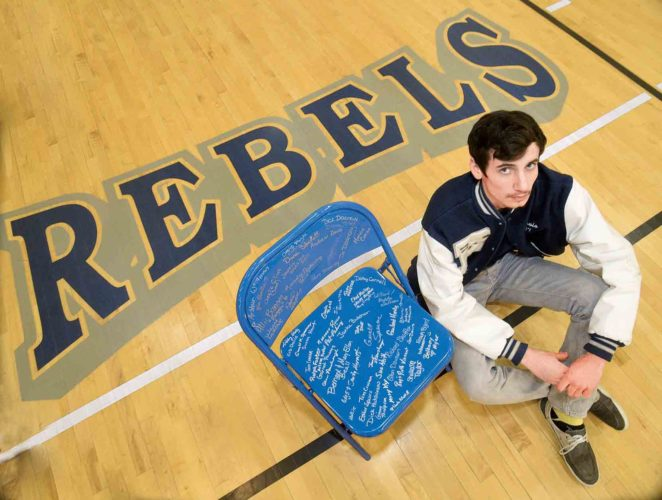 Photo by Jeff Baughan Ritchie County High School senior Travis Pickering sits beside his senior project, a chair honoring the memory of his father, Randy.