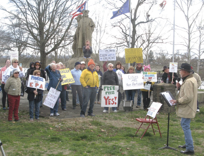 Photo by Jeffrey Saulton Jim Rapp, at right, of Marietta, addresses the crowd on health care issues at Muskingum Park, next to a chair reserved for Rep. Bill Johnson who organizers said was invited but did not attend.