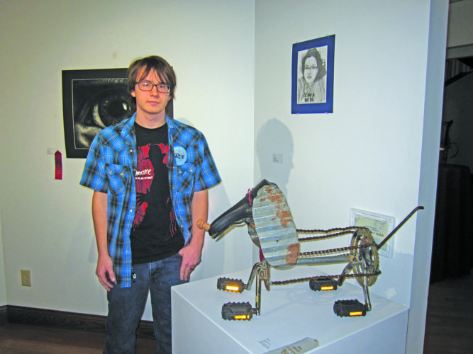 Photo by Wayne Towner Brendon Stout, of Weston, a senior at Lewis County High School, stands with the sculpture he submitted for the West  Virginia Art Educators Association display at the Parkersburg Art Center.