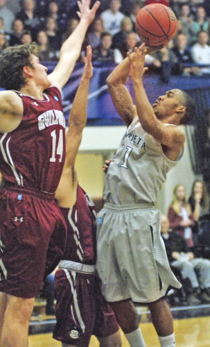 Marietta College's Keith Richardson (11) goes up for a basket as Guilford's Carson Long (14) defends during an NCAA Division III men's basketball tournament game Saturday at Ban Johnson Arena. Richardson finished with 19 points as the Pioneers won, 88-64. Photo by Jordan Holland.