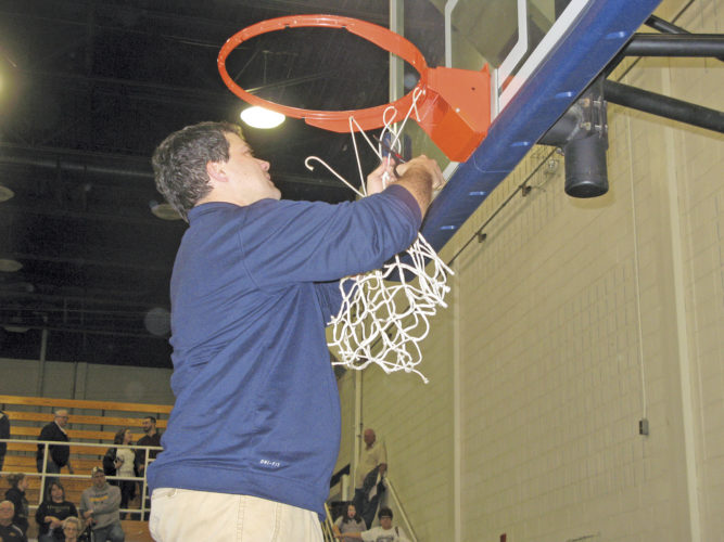 Ritchie County head girls basketball coach Dave McCullough cuts down the last of the net following Thursday night's 47-42 victory against Cameron in a Class A Region I co-final, which punched the Rebels' ticket to this week's state tournament in Charleston. Photo by Jay W. Bennett.