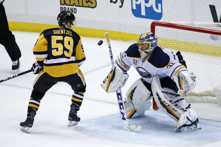 Pittsburgh Penguins' Jake Guentzel (59) deflects the puck past Buffalo Sabres goalie Anders Nilsson (31) for a goal in the third period of an NHL hockey game Sunday in Pittsburgh (AP Photo).