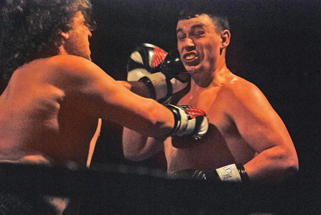 Calhoun County graduate Andrew Satterfield, right, reacts after taking a punch from Clarksburg's Brandon Perkins during their amateur kickboxing match Saturday at Fieldhouse Fight Night 6 inside Parkersburg High School. Satterfield defeated his opponent via unanimous decision. Photo by Jay W. Bennett.