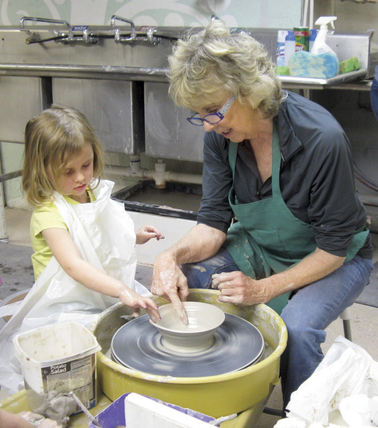 Photo by Jeffrey Saulton Addie Renner, left, helps her grandmother Jan Whitman make a bowl during the Art-O-Rama at the Parkersburg Art Center on Saturday.