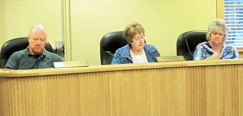 Belpre City Council members, from left, Brian Turrill, Donna Miller and Susan Abdella, review papers during Monday's meeting. Council gave final approval Monday for a contract to provide daytime emergency squad service in Belpre. (Photo by Wayne Towner)