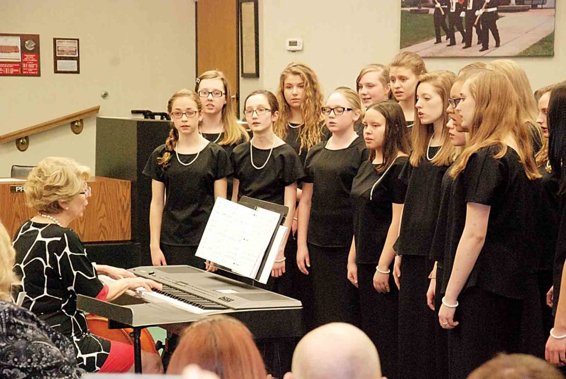 "The Smoot Theatre Girls Ensemble performs ""O Danny Boy,"" under the direction of Cathy Martin, left, during Tuesday's Parkersburg City Council meeting in council chambers. The Smoot's Girls and Boys Ensembles and Children's Chorus were recognized by council with Youth Achievement Awards. (Photo by Evan Bevins)"