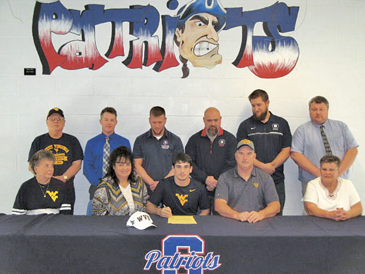 Parkersburg South's Hunter DeLong signed his national letter of intent on Wednesday afternoon to continue his wrestling career at West Virginia University. Pictured at the ceremony were, front row, from left, grandmother Linda Maxwell, mother Paula DeLong, Hunter DeLong, father Chris DeLong and grandmother Gloria DeLong. Back row, from left, grandfather Richard Maxwell, head baseball coach Matt Null, head wrestling coach Shaun Smith, head football coach Mike Eddy, assistant football coach Cody Nutter and youth mat coach Tim Amos. Photo by Jay W. Bennett.