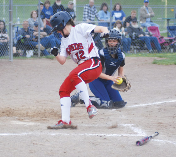 Warren catcher Chloe Corser looks on in disbelief after Parkersburg's Maddi Leggett eluded her tag by side stepping into the field of play during Thursday's game at Jackson Park. Leggett reached back and touched the plate to score one of the Big Reds' five runs in the fourth inning of the red and white's eventual 8-7 victory against the Warriors. Photo by Jay W. Bennett.