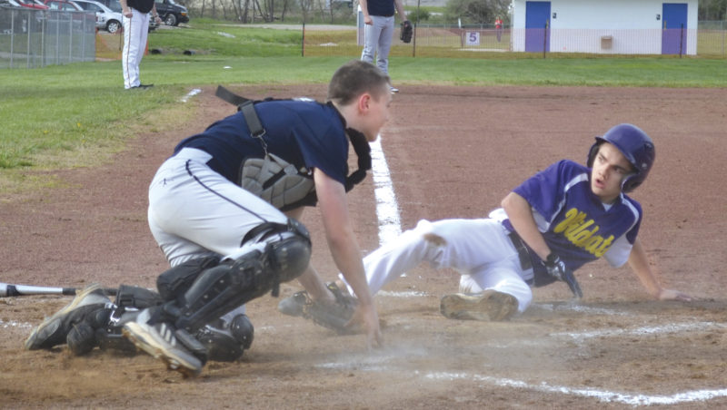 Wood County Christian's Josh Stoia, right, eludes Grace Christian catcher Cooper Branson's tag at the plate duirng third-inning action at Jackson Park Thursday. The Wildcats won, 16-2. Photo by Ron Johnston.