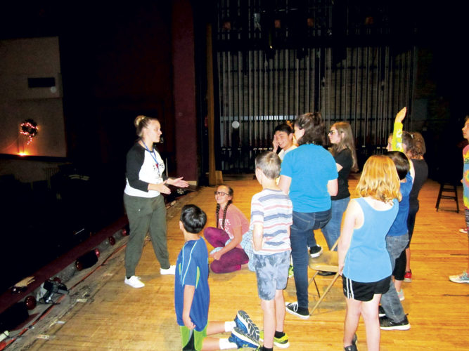 """Photo by Wayne Towner Caroline Clay, at left, a tour director with Missoula Children's Theatre, works with a group of local students on the Smoot Theatre stage in preparation for two performances of the show """"Peter and Wendy"""" on Saturday."""