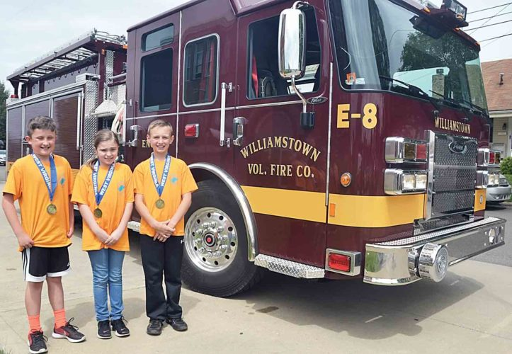 Williamstown Elementary School fourth-graders Brody Bowyer, Navaeh Hansen and Parker Schramm were given a ride in a Williamstown Fire Department fire truck Tuesday for winning a first place prize at the West Virginia Social Studies Fair. (Photo by Brett Dunlap)