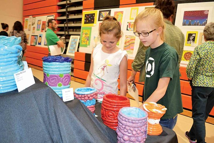 Photo by Peyton Neely Phillips Elementary third-grader Brooke Hall, 9, and Marietta Middle School student Cassidy Graham, 12, look at art displayed at the Marietta City Schools Fine Arts Festival on Wednesday evening in the high school's gym.