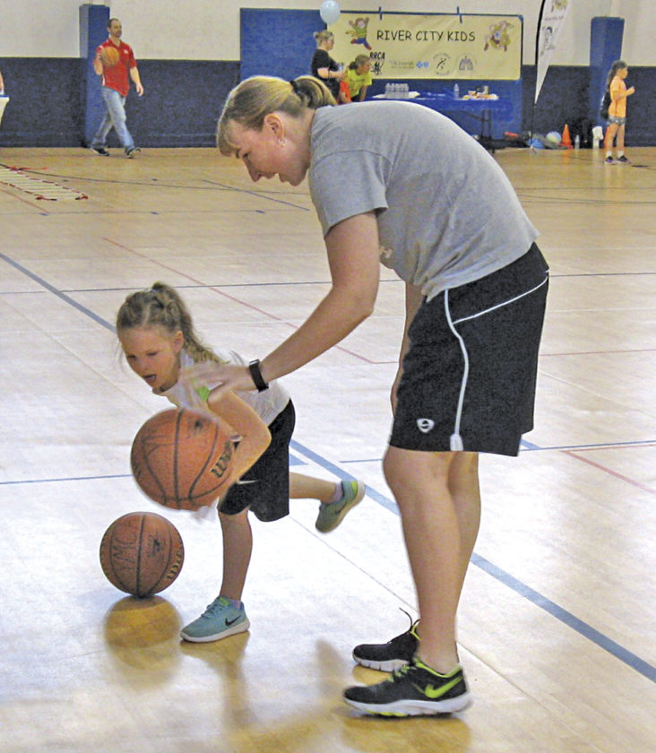 Photo by Jeffrey Saulton Addison Walton dribbles a basketball with Ann Skufca, program director at the YMCA.