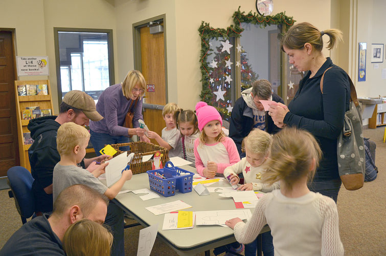 Children make paper decorations depicting the Turkish saint, St. Nikolaus for an early St. Nikolaus Day celebration at the Public Library Saturday. Librarians read stories about St. Nikolaus, the Turkish saint who's special day is celerbated on Dec. 6 with gifts for good children, and lumps of coal for the naughty ones. Children also made paper decorations, and sang German Christmas carols.