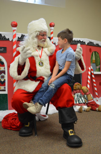 Blake Lienig sits on Santa's lap during the Sertoma Club's Breakfast with Santa fundraiser for Santa's Closet, at the Cathedral of the Holy Trinity Sunday. Staff photo by Connor Cummiskey