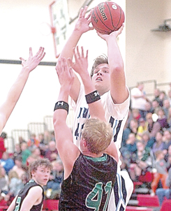 Staff photo by Steve Muscatello Minnesota Valley Lutheran's Nick Fischer takes a shot over West Lutheran's Ben Beise (41) Tip-Off Tournament Friday at Martin Luther College in New Ulm. For more photos of this event go to cu.nujournal.com