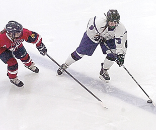 Staff photo by Steve Muscatello New Ulm's Caleigh Heck keeps the puck inside the offensive zone despite pressure from Emma Sternberg of Orono on Saturday at the New Ulm Civic Center. For more photos of this event go to cu.nujournal.com