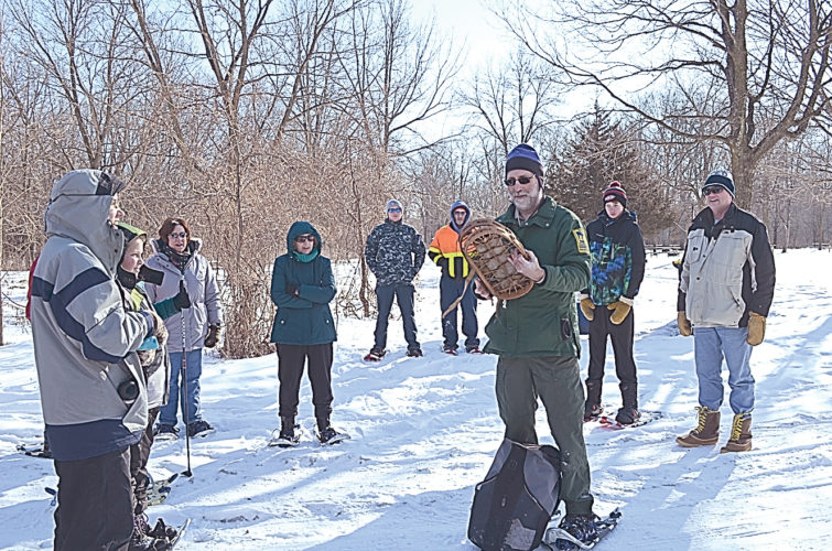 Staff photo by Connor Cummiskey Minneopa Area Naturalist Scott Kudelka shows the hikers a pair of bear paw snowshoes that he estimates are from the 1950s. He explained the shoes were good for flat, wooded areas but because they lacked a upward curve on the front it would be easy to dig them into the snow and trip.