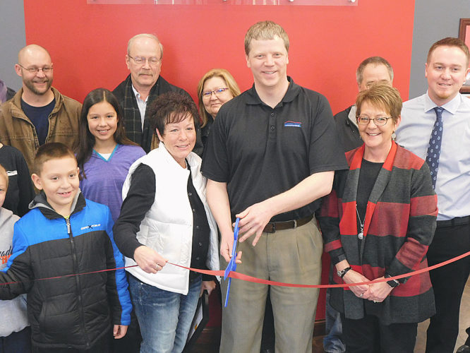 Staff photo by Clay Schuldt American Family Insurance agent, Brian McCabe, prepares to cut the ribbon officially opening the new building to the public.